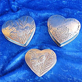 Pewter cremation urns - small heart shaped urns with decorative etchings.